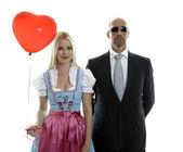 Frau im Dirndl mit rotem Herzballon und Leibwächter