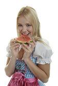 Frau im Dirndl isst Wassermelone