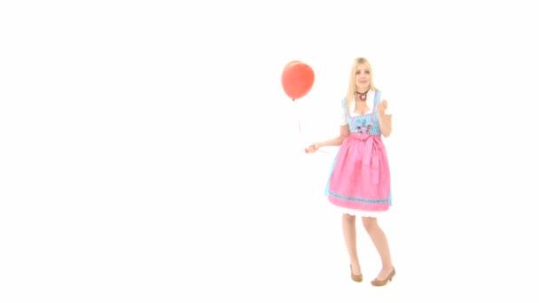 Frau im Dirndl mit herzförmigem Ballon