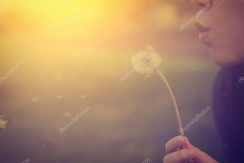 Girl blowing on white dandelion