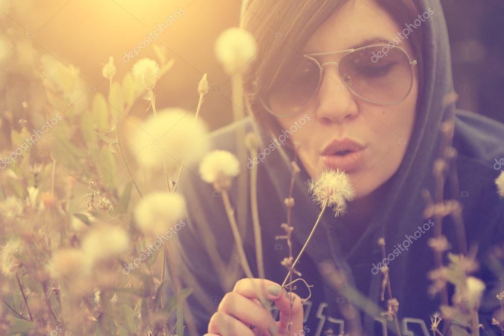 Woman blowing dandelion