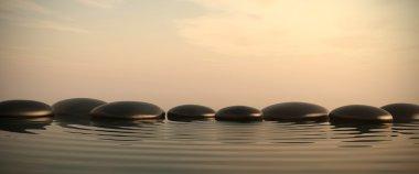 Zen stones in water on sunrise