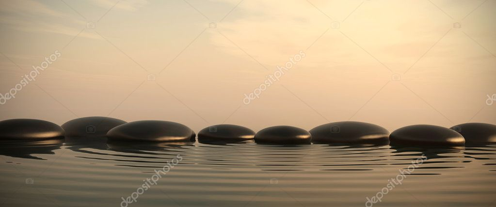 Zen stones in water on sunrise