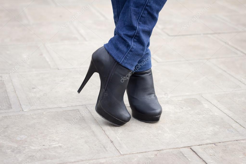 Pierna de la chica con botas negras en un tacón alto. — Foto