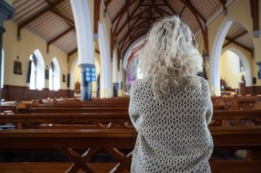 Woman praying in church from behind
