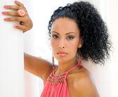 Egy fiatal fekete nő, a divat, a rózsaszín ruha és fülbevaló, afro frizura modell-portré