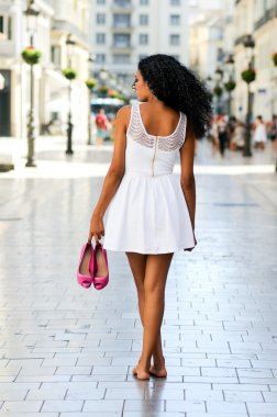 Black woman, afro hairstyle, walking barefoot on a commercial st