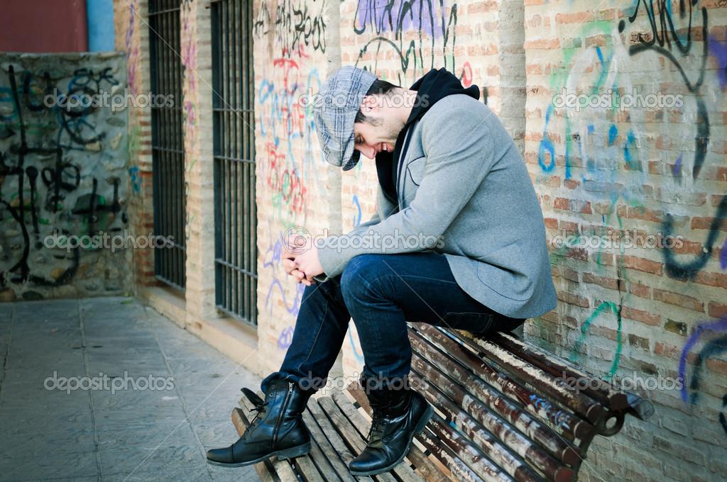 Retrato de hombre guapo en fondo urbano con un gorro de