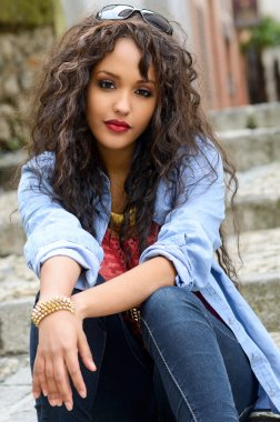 Attractive mixed woman in urban background wearing casual clothe