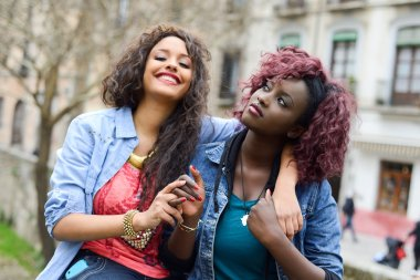Two beautiful girls in urban backgrund, black and mixed women