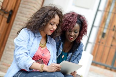 Two beautiful girls with tablet computer in urban backgrund