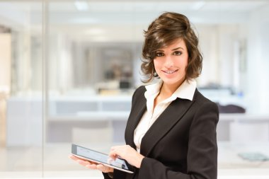 Young pretty business woman with tablet computer in the office
