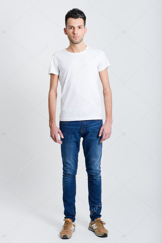 Serious young man standing against white background for Homme debout meuble