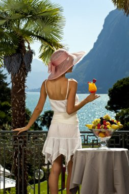 Beautiful woman with cocktail on the terrace