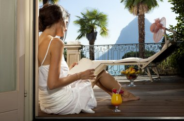 Beautiful woman reading on the terrace