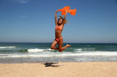 Beautiful tanned woman jumping on beach