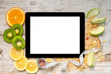 tablet computer with fruit and a measuring tape for weight loss