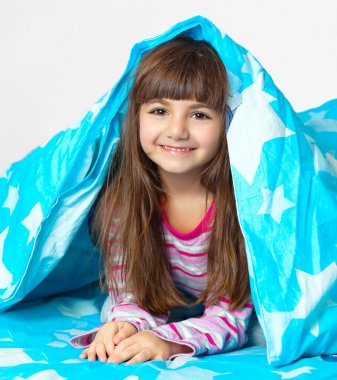 beautiful little girl lying in bed under a blue blanket