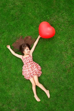 beautiful girl lying on the grass and holding a red ball in the