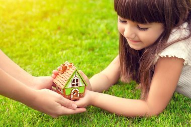 little girl and a woman hands holding small house on a backgroun