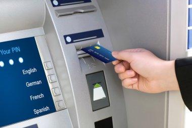 men hand businessman puts credit card into ATM