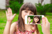 Photo female hand holding a phone with video call of little girl on th