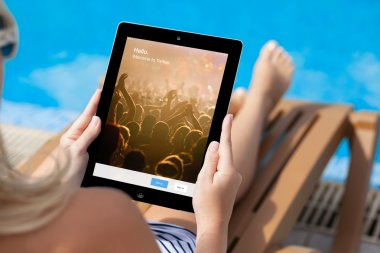 Girl lying on a sun lounger by the pool and holding iPad with Tw