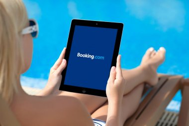 Girl lying by the pool and holding ipad with Booking on the scre