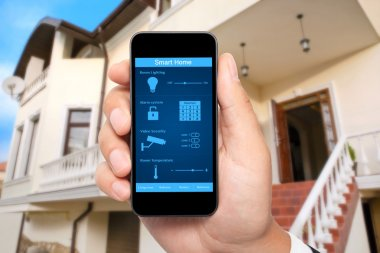 Male hand hold a phone with system smart house on the background