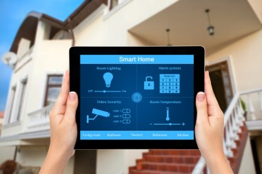 Female hands hold a tablet with system smart house on the backgr