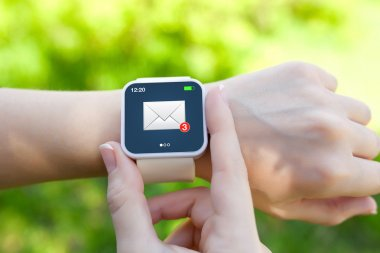 Isolated female hands with white smartwatch with email on the sc