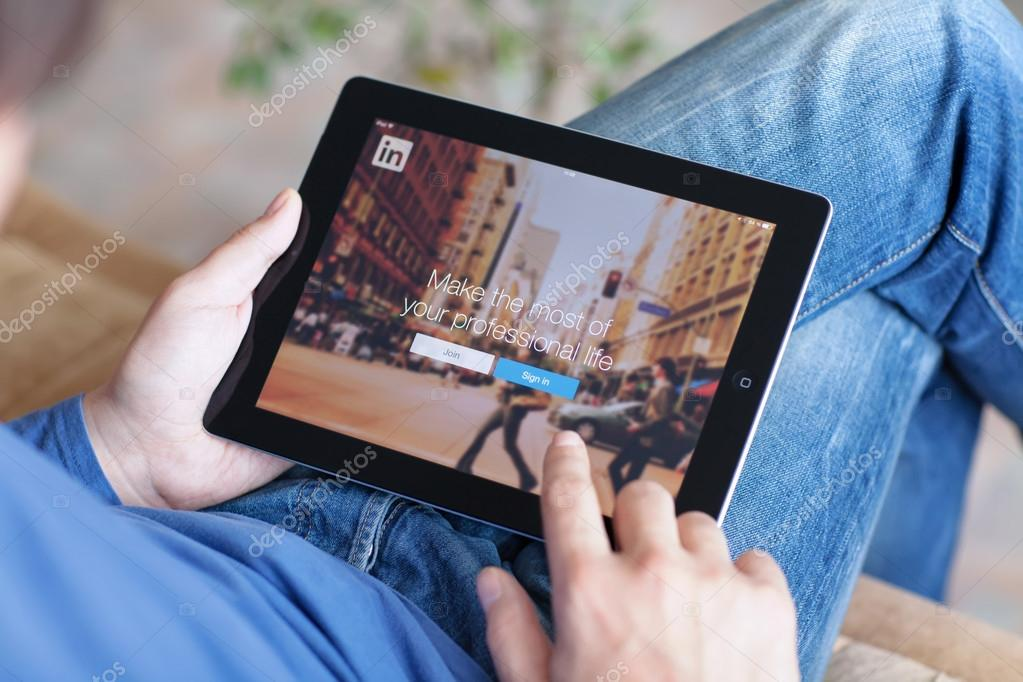 Man sitting on the sofa and holding iPad with App LinkedIn on th