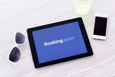 iPad with app Booking on the screen lies on a table with glasses