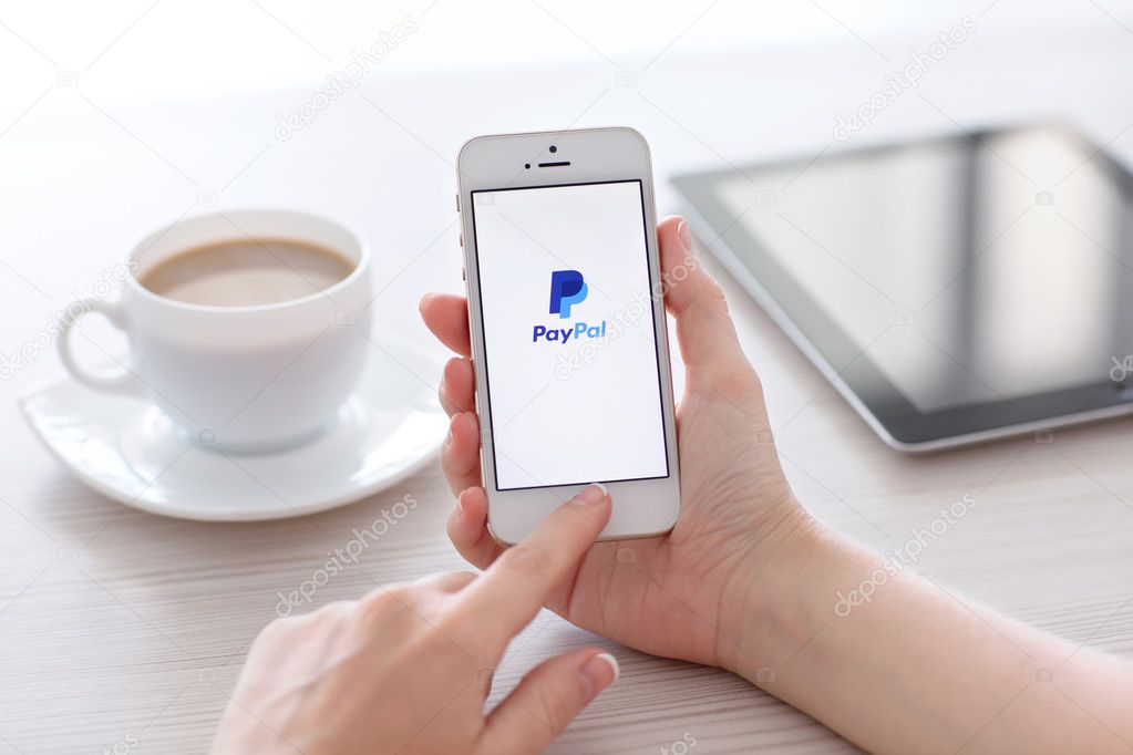 Female hands holding white iPhone 5s with app PayPal on the scre