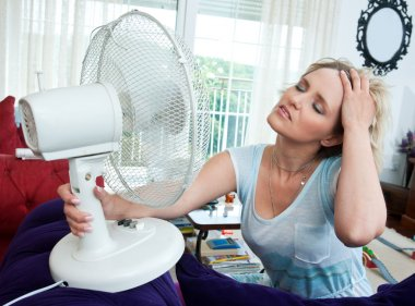 Woman cooling herself with fan stock vector