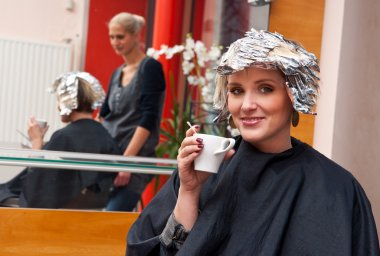 woman relaxing over coffee in hair salon