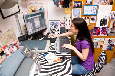 teen girl in messy room on computer