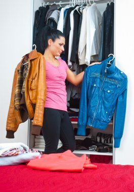 attractive woman in front of closet full of clothes