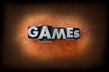 The word games made from vintage lead letterpress type on a leather background. stock vector