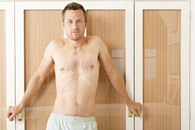 Attractive man in front of wardrobe doors in a bedroom in underwear