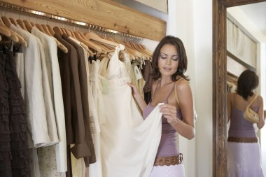 Young attractive woman looking at clothes in a fashion store.
