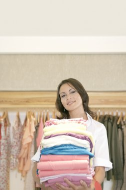 Store attendant holding a pile of clothes in a fashion shop.