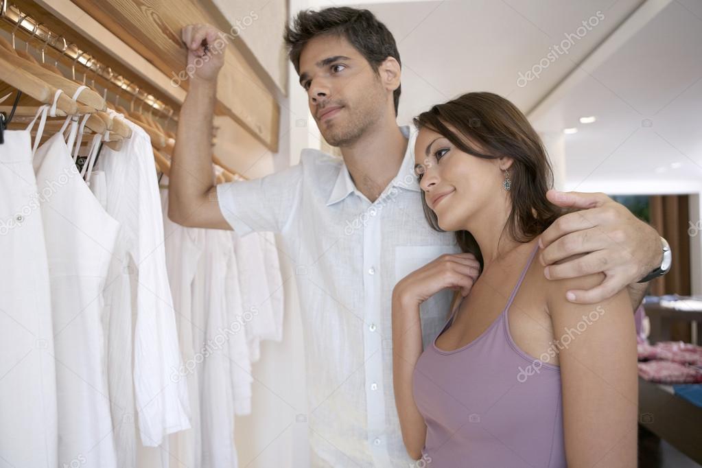 71dda5cf14ff41 Jonge aantrekkelijke paar kijken naar kleren in een mode-winkel — Stockfoto