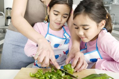 Mum chopping vegetables with twin daughters in a family home kitchen.