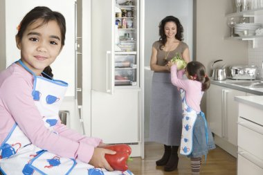 Young mum taking vegetables out of the fridge in a home kitchen with twin daughters.