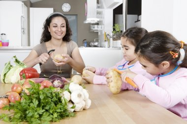 Mum and twin daughters peeling poratoes at a kitchen's table.