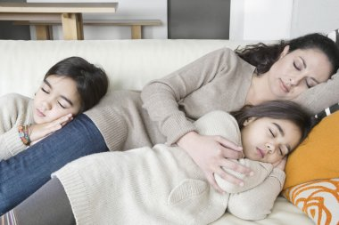 Portrait of a mother and two twin daughters sleeping on a sofa.
