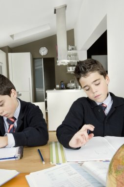 Two identical twin brothers doing their homework on the kitchen table.