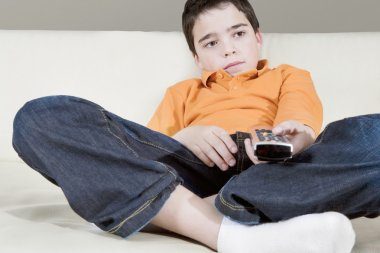 Young boy using a tv remote control while watching television sitting on a white leather sofa at home.