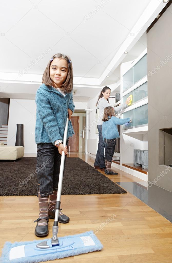 Mother and daughters cleaning the house together smiling for House cleaning stock photos